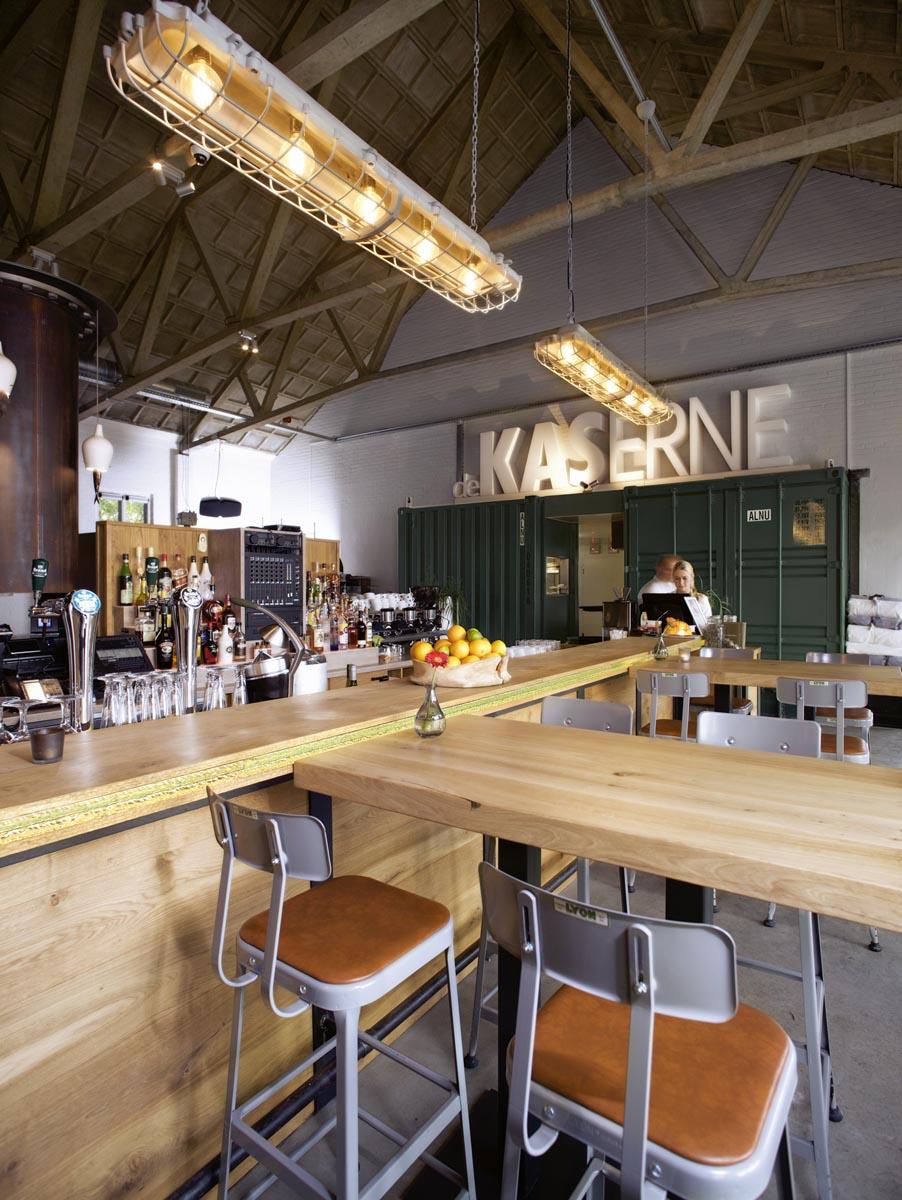 5 metalen barkruk aan massief eiken bar van restaurant De Kaserne in Den Bosch met stoere industriele verlichting boven bar
