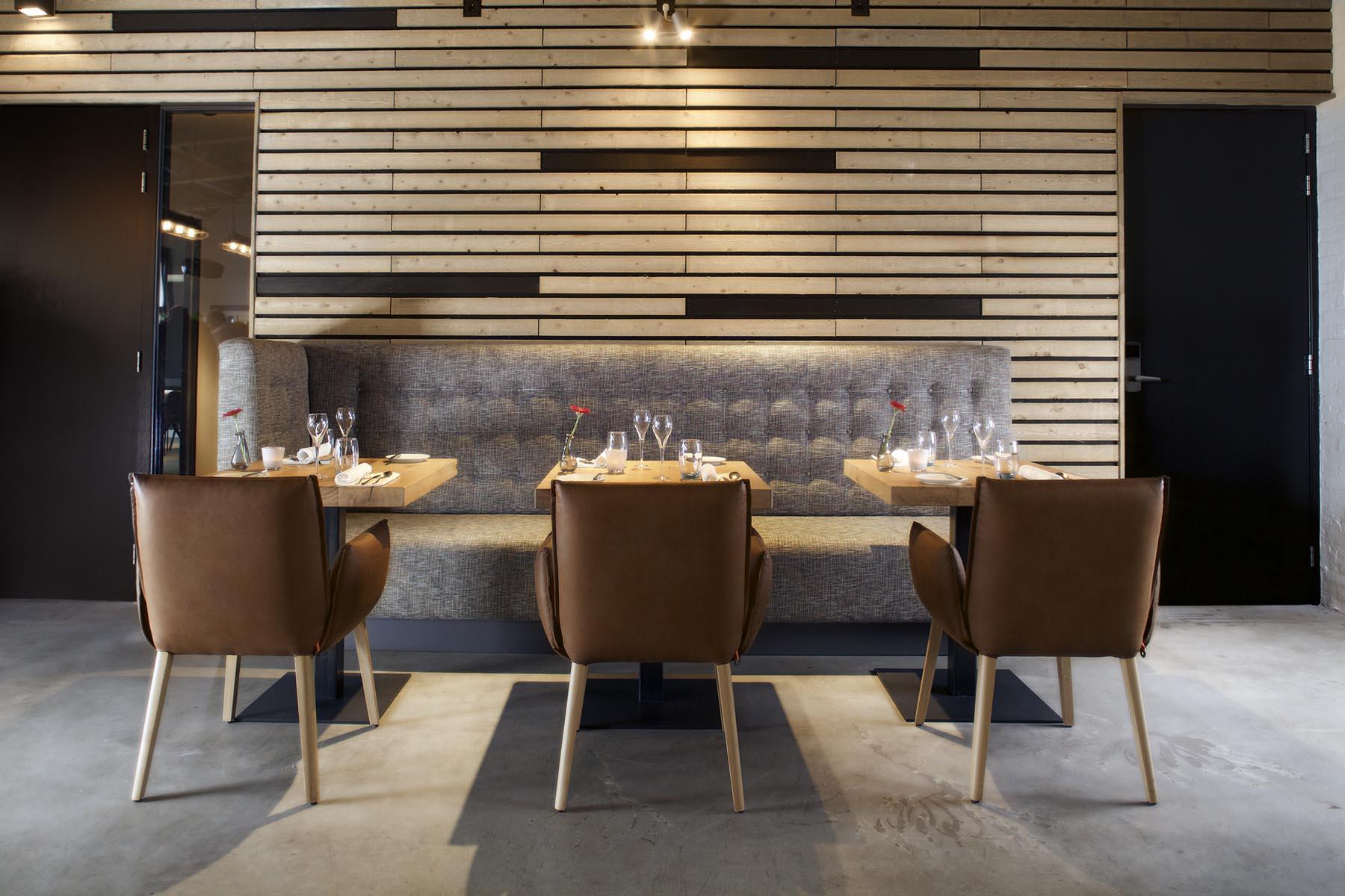 6 akoestische wand met latten en schapenwol erachter voorin zitbank met eiken houten tafels en fauteuils in leer