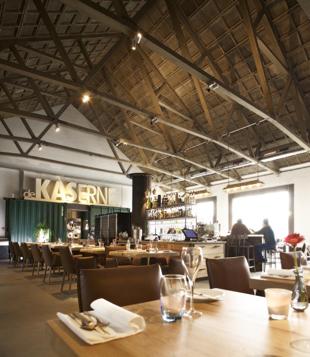 1 interieur restaurant De Kaserne met eiken tafels vrijstaande bar heerlijke fauteuils en mooi verlichte betonnen spanten