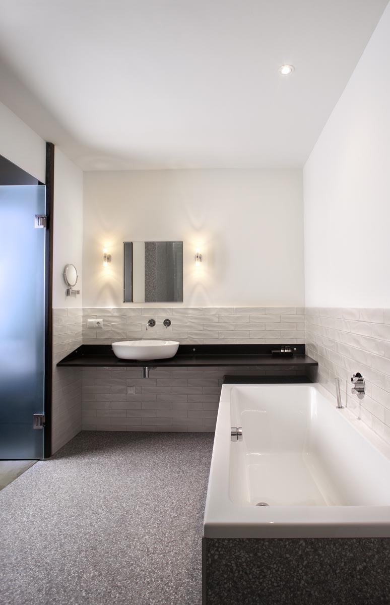 11 Badkamer in suite van hotel restaurant De KASerne in Den Bosch met stalen meubel stoere wandtegels en terazzo vloertegels