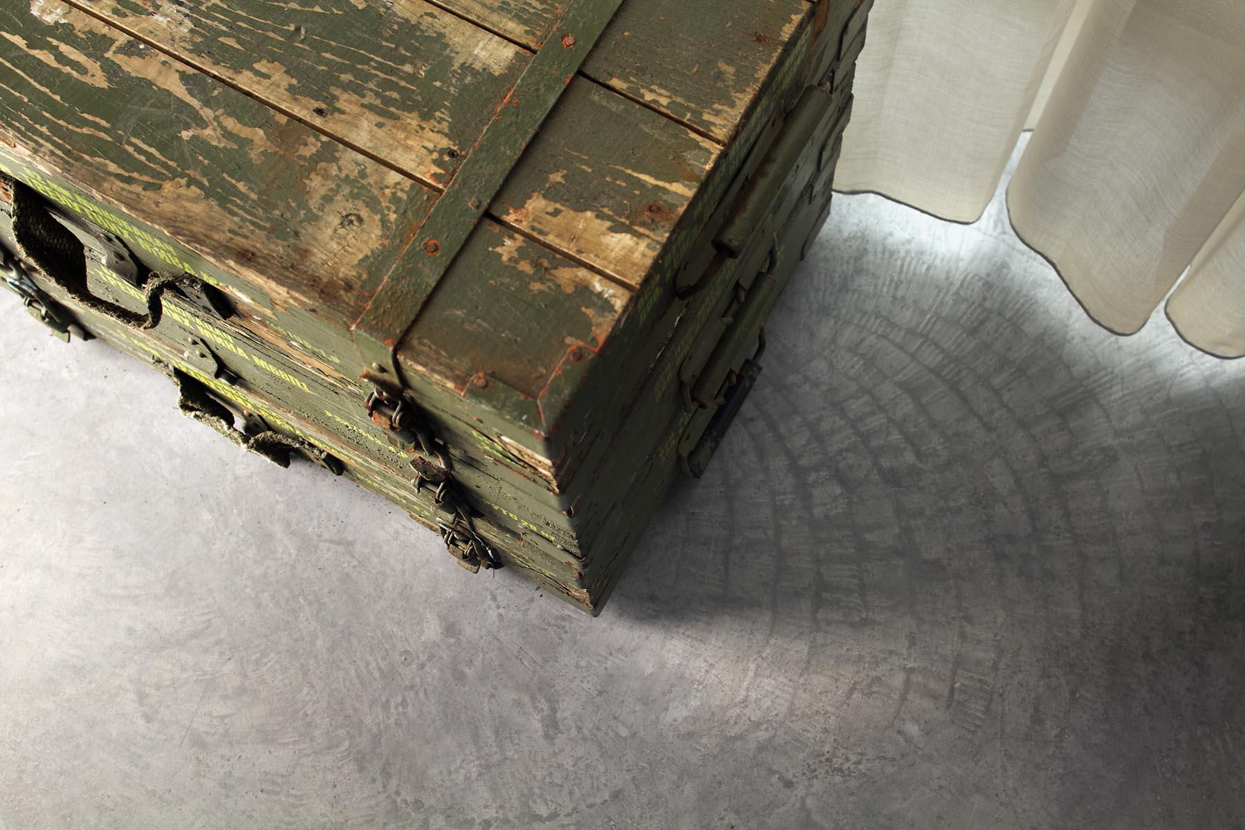 16 Betonnen vloer in hotelkamer van De Kaserne in Den Bosch met oude legerkisten ter decoratie