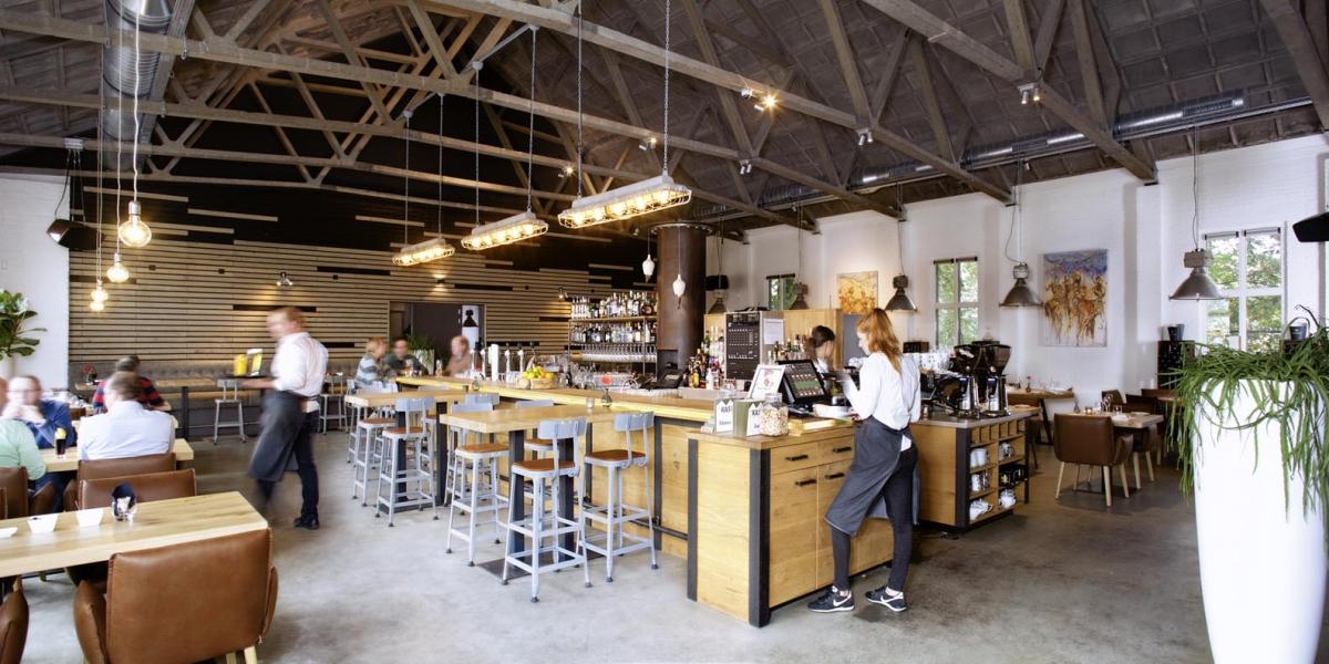 3 interieur restaurant De Kaserne Den Bosch met betonnen vloer stoere verlichting fauteuils