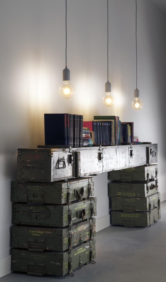 8 In de gang van hotel De Kaserne in Den Bosch is ruimte voor boeken op een oude raketkist en legerkisten